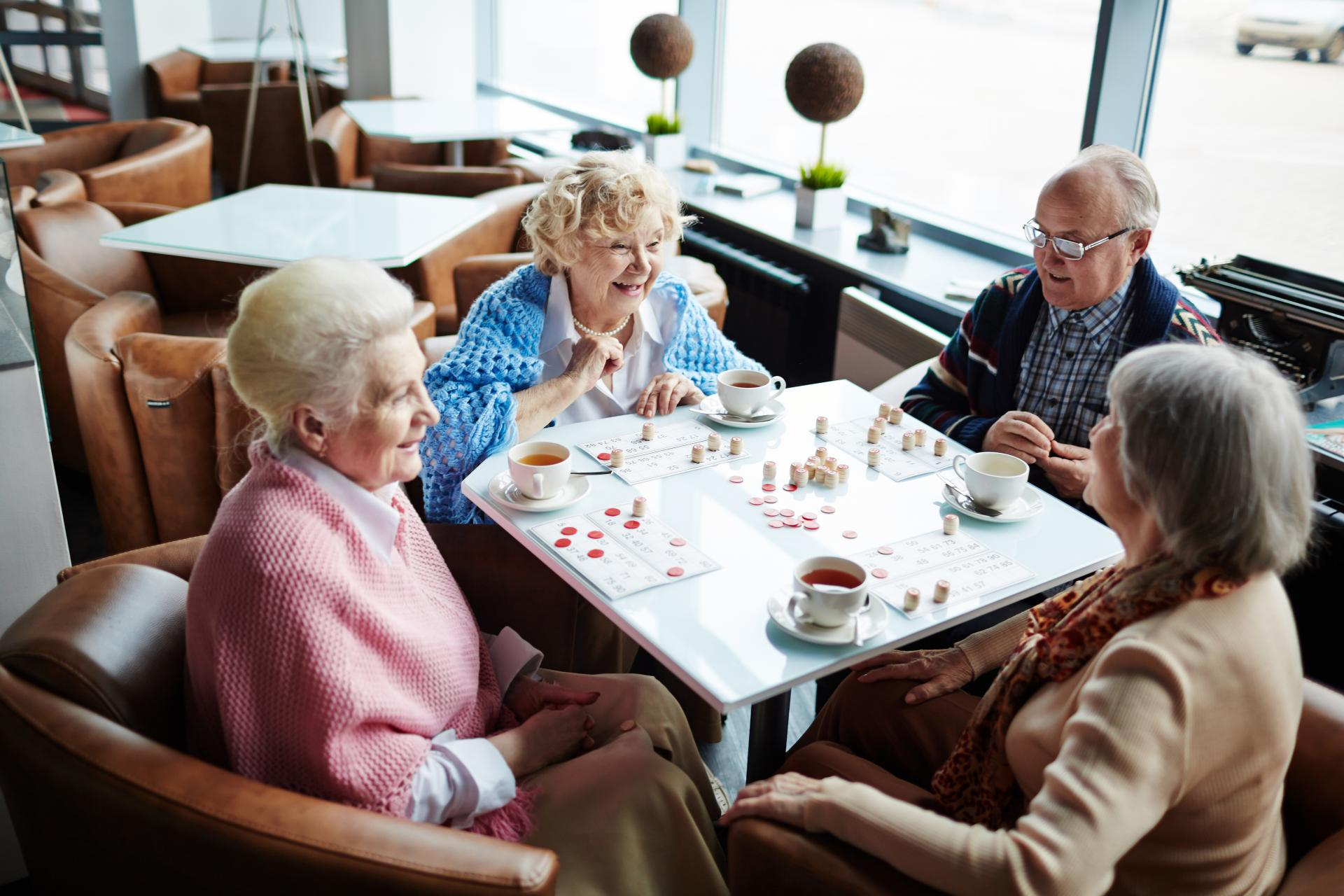 Carless + Adams care home residents playing a board game in the communal living space