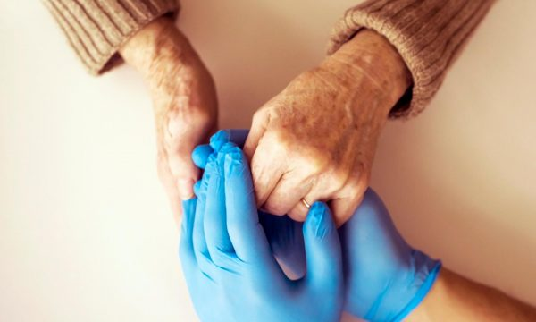 Care home visitor and resident holding hands